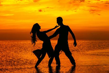 Silhoette горячей танцевальной пары на фоне золотой тропический закат на море.