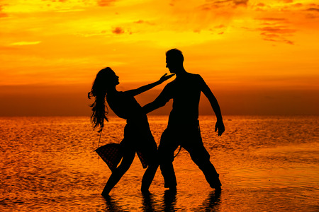 Silhoette of hot dancing couple at golden tropical sea sunset background.