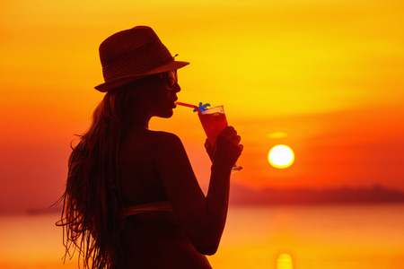 Closeup portrait of woman in hat with cocktail at tropical red sunset background. Standard-Bild