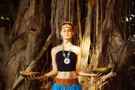 ethnic dress: Beautiful young girl in ethnic dress is standing with closed eyes near banyan tree and holding two halfs of watermelon. Stock Photo