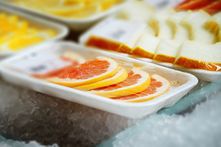 shopwindow: Closeup image of package of slices oranges and melons with ice around at shopwindow background. Stock Photo