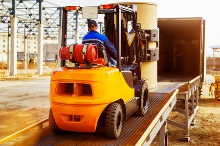 Автопогрузчик ставит груз со склада в грузовике на открытом воздухе