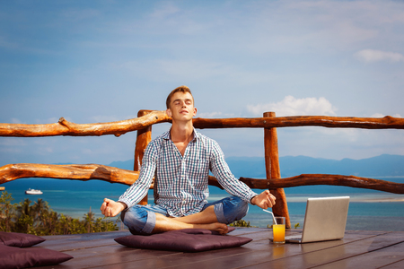 meditaion: Happy young man with closed eyes is sitting in yoga pose with closed eyes at wooden restaraunt at natural summer mountain view background.