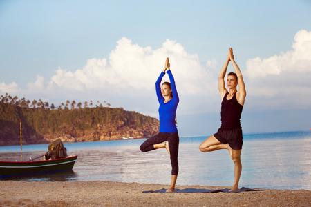 El par joven está practicando yoga en la salida del sol de oro fondo del mar.