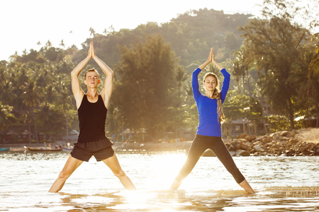 Fitness, sport, and lifestyle concept - couple is exercising making yoga  at  tropical sunrise background.