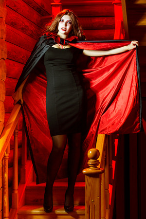 Vampire woman in cloak is standing indoors at stairs with red light background. Halloween holiday concept. Stock Photo