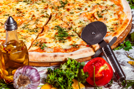 vegeterian: Tasty italian vegeterian pizza with fresh golden cheese, garlic and tomato at wooden background.