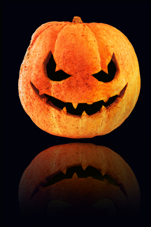 Halloween symbol. Orange jack o lantern pmpkin awith reflection at black background.