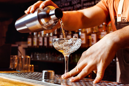 Male bartender is making cocktail pouring alchohol from shaker to glass at bar background.