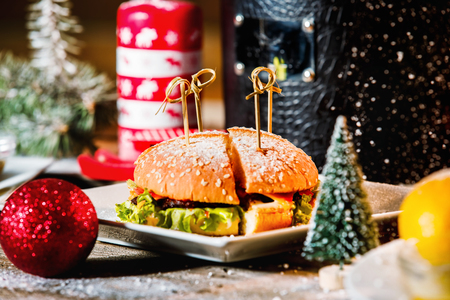 Closeup image of hamburger on white plate at Christmas style decorated wooden background. Stock fotó