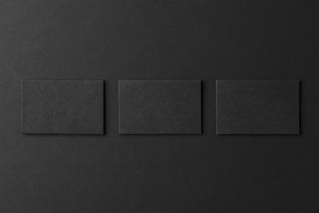 Mockup of three blank business card stacks at black textured background. Standard-Bild