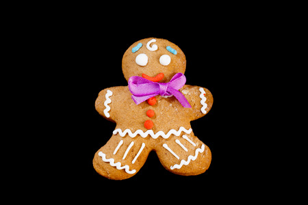 Closeup image of gingerbread man isolated at black background.