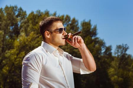 hombre fumando puro: Portrait of elegant man smoking cigar outdoors.