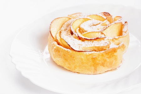 Sweet rose style twisted cake of pastry puff on plate isolated at white background.