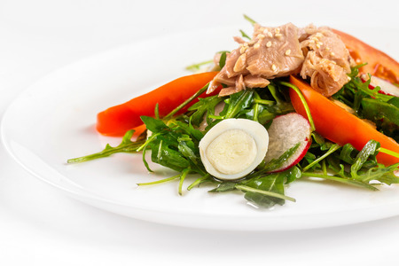Plate of tuna salad with fresh vegetables isolated at white background.