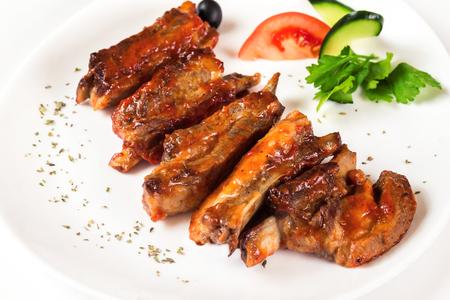 Assiette d'ailes et de jambes de poulet dorées frites isolées sur fond blanc.