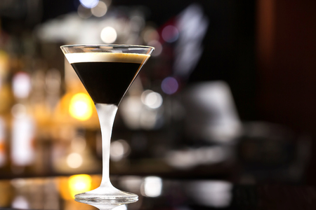 amaretto: Glass of black russian cocktail at bar counter background.