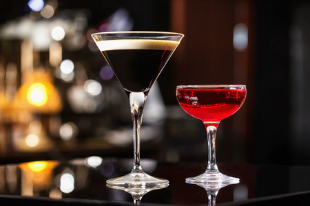 sweet vermouth: Manhattan and espresso cocktails in elegant glasses at colorful dark bar stand background.