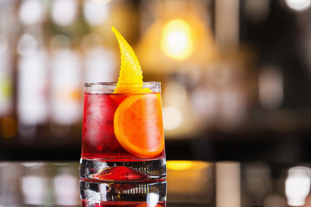 Closeup glass of negroni cocktail decorated with citrus at bar stand festive background.