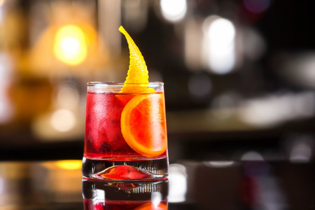 sweet vermouth: Closeup glass of negroni cocktail decorated with citrus at bar stand festive background.