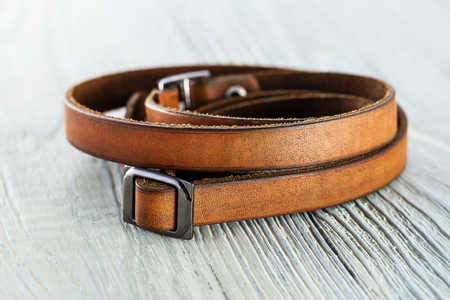 Pulsera de cuero marrón remolino en el fondo de luz de madera del tablero. Foto de archivo