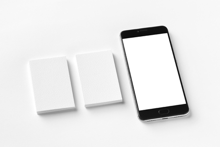 Mockup of two blank vertical business cards and cell-phone isolated at white textured paper.