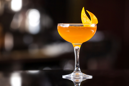 Glass of orange cocktail decorated with lemon at bar counter background.