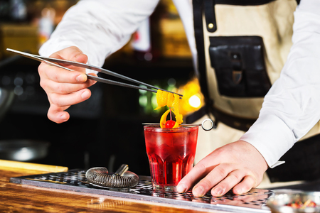 Bartender is holding orange rind in tongs decorating red cocktail at bar background. Stock Photo