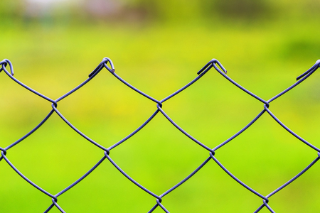 Closeup image of mesh wire fence at green grass outdoors background.