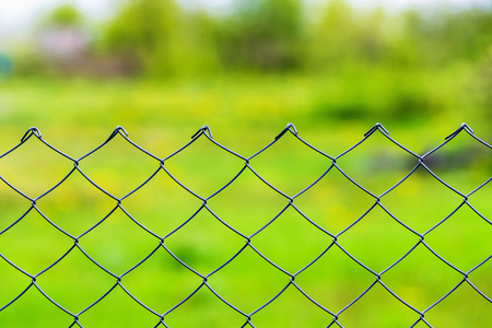 Closeup image of mesh wire fence at green outdoors background.