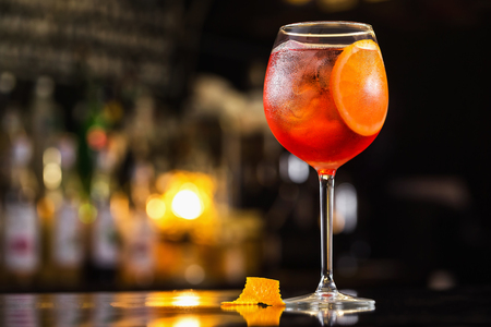 Closeup glass of spritz aperol cocktail decorated with orange at bright bar counter background.