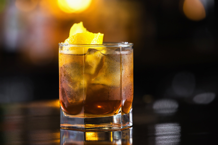 Closeup image of glass of rum and cola cocktail at bright blurred background.
