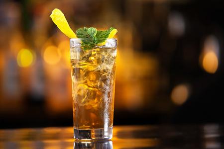 バーのカウンターの背景でミントで飾られたロングアイランド アイス ティー カクテルのグラスをクローズ アップ。