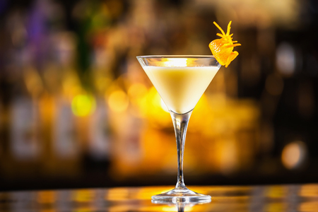 Closeup glass of egg liquor decorated with orange at bright bar counter background. Stock Photo