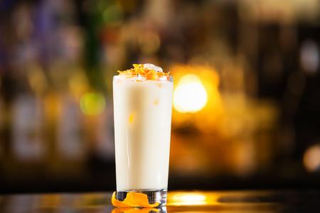 Closeup glass of pina colada cocktail at bright bar counter background.