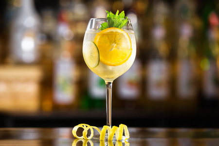 Closeup glass of white sparkling wine sangria decorated with citrus slices at bright bar counter background. Standard-Bild