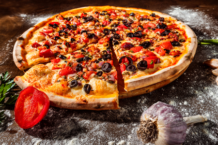 Closeup image of tasty italian pizza with cheese, tomato, olives and ham at wooden board background. Stock Photo