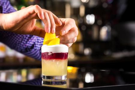 adding: Closeup image of bartender hands decorating cocktail with lemon at dark backgrpund. Stock Photo