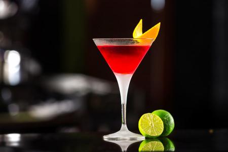 コスモポリタン カクテル バーの背景にオレンジで飾られたガラスのクローズ アップ。