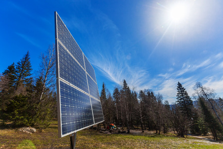 voltaic: Solar battery at spring Russian sunny forest background with blue sky.