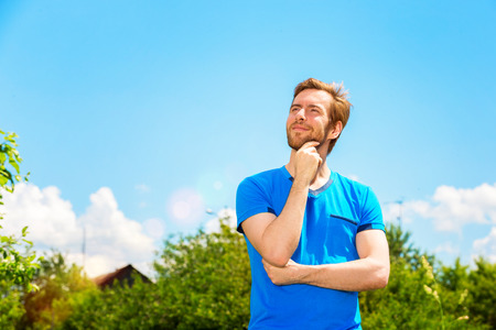Closeup portrait of thoughtful happy bearded man standing at summer park background.