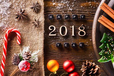 Closeup Happy 2018 New Year caption and decoration set at wooden table as greeting card background.