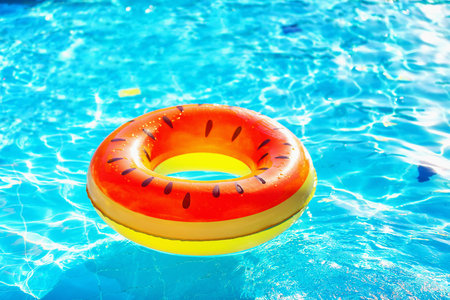 lifeline: Closeup image of watermelon style inflatable circle floating at swimming pool.