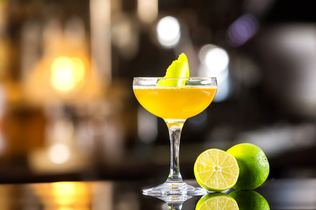 Closeup image of daiquiri cocktail decorated with lemon at bar counter background.