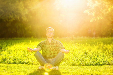 Portrait of serene meditating man in a park at summer golden sunset background.