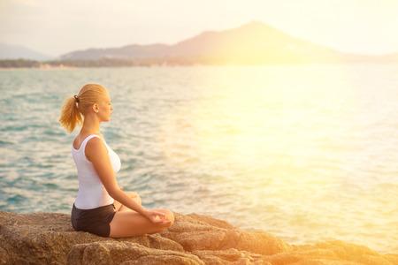 Молодая женщина практикует йогу на камне на фоне тропического моря восход солнца. Фото со стока