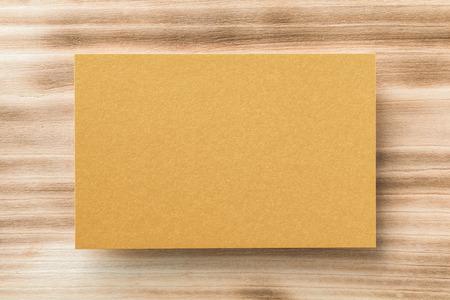 Макрофотография макет пустой золотой горизонтальной визитной карточки на фоне естественного дерева. Фото со стока