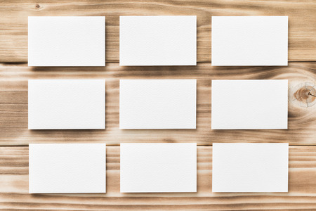 Макрофотография макет из девяти пустых вертикальных визитных карточек на светлый естественный деревянный фон.