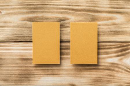 Макрофотография макет из двух золотых пустой вертикальных визитных карточек на светлом фоне естественного дерева.