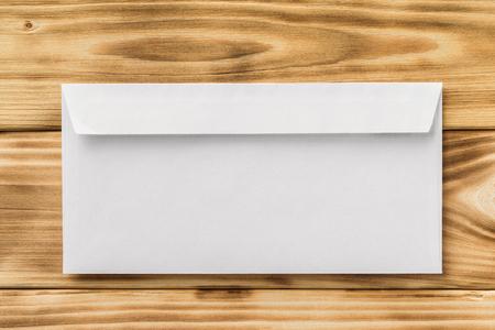 Макет из белого закрытого конверта на фоне текстурированных деревянных столов. Фото со стока